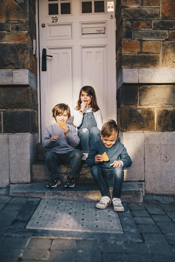 Enfants assis sur le porche d'une maison ancienne