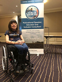 Woman sitting in a wheelchair sitting in front of their banner smiling