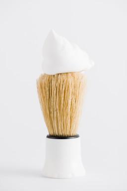 foam-synthetic-shaving-brush-against-whi