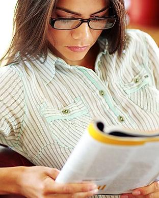 Businesswoman reading magazine in modern