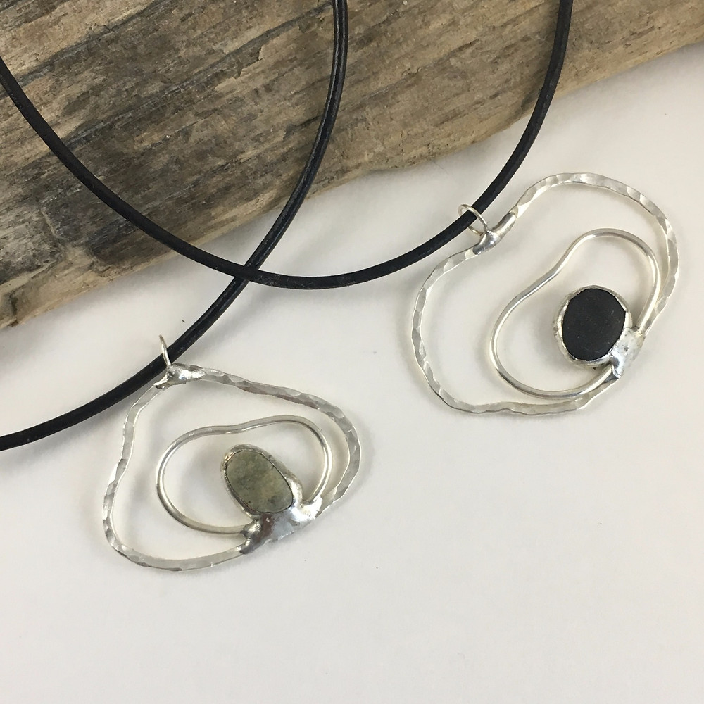 Hand forged oyster style pendants in sterling silver with a pebble in its center