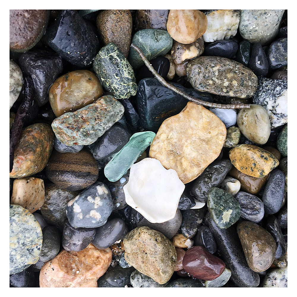Sea glass hiding in pebble mix on a beach