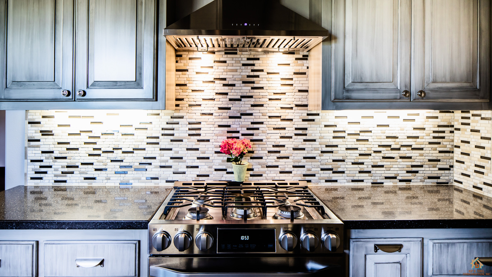 Glazed White Lacquer Kitchen with drawer pulls, solid surface countertops and glass tile backsplash.