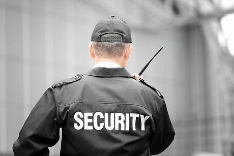 Male security guard using portable radio