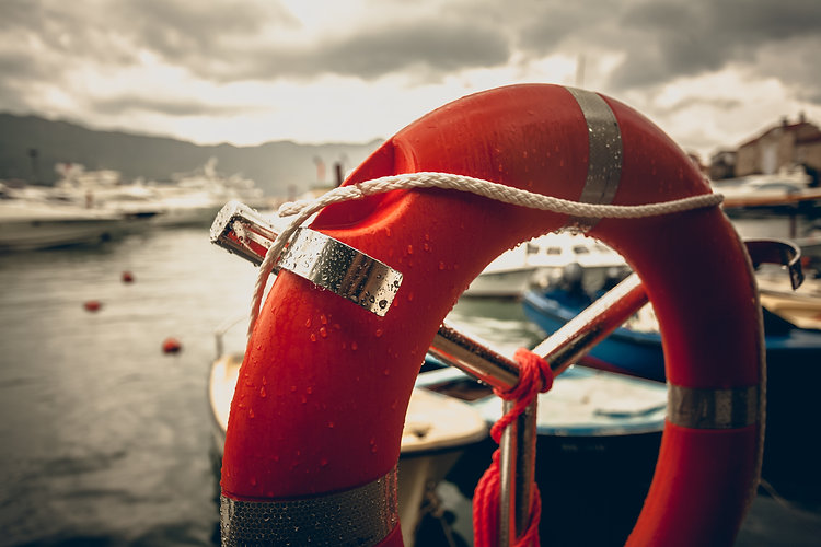 Toned photo of red lifebuoy at rainy weather in seaport .jpg