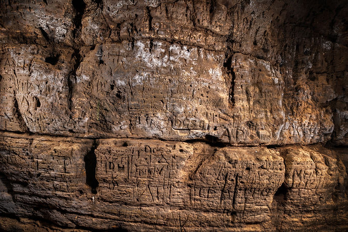 Ancient carvings on the wall of one of the historic site caves at Caves of Hella in Iceland