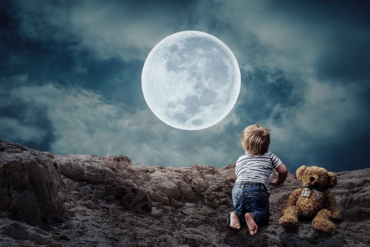 Bambino che guarda la luna con orsacchiotto