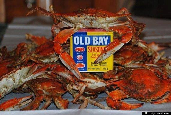 A pile of cooked crabs with one hugging some Old Bay Seasoning