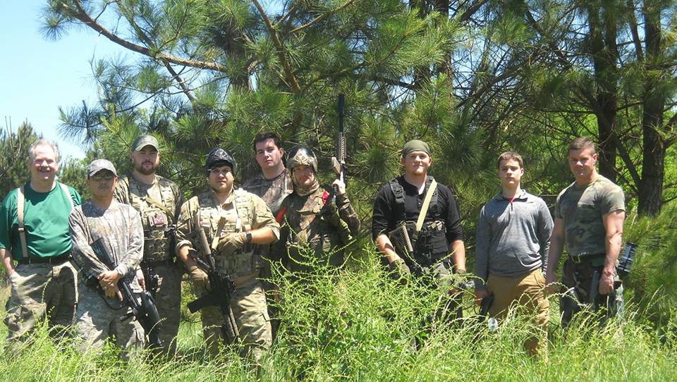 Derek and 8 friends in camo, some holding paintball guns
