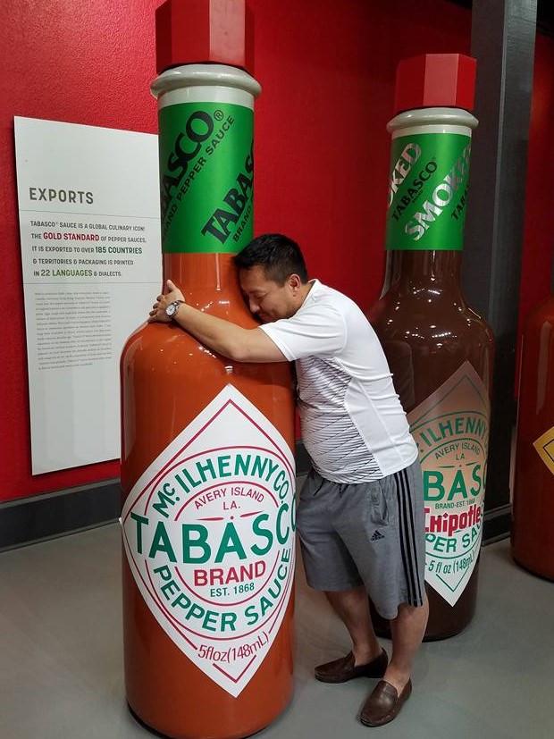 Derek hugging a giant bottle of Tabasco