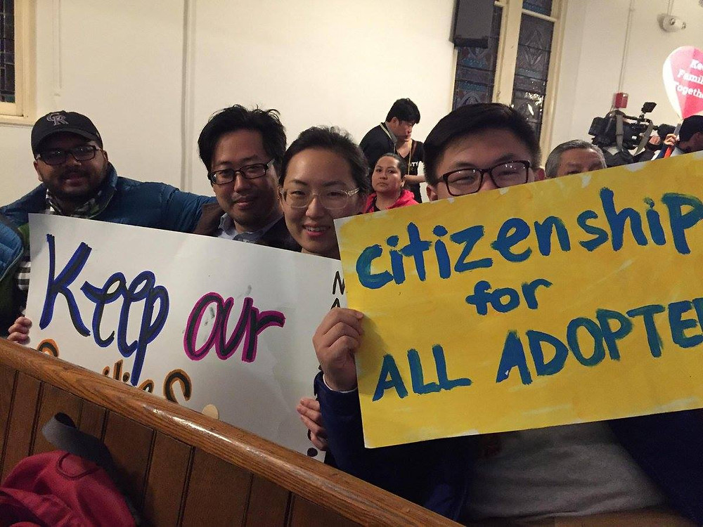 "Adoptees with protest signs reading, ""Citizenship for All Adoptees"""