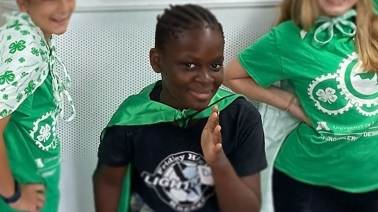 4H student smiling and gesturing to camera.
