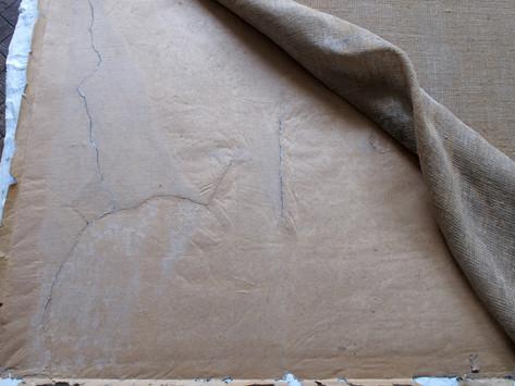 stav v průběhu čištění a scelování trhlin v papírové podložce