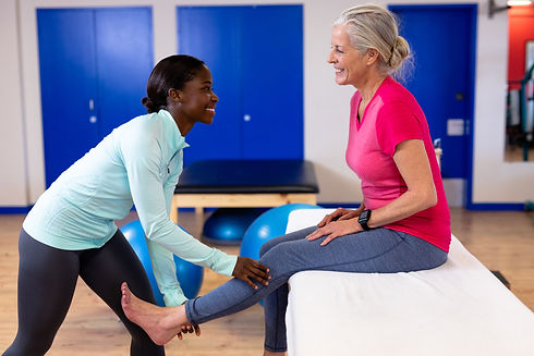 Happy female physiotherapist giving leg massage to active senior woman in sports center. S