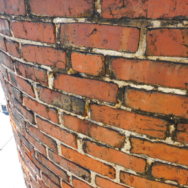 Brick masonry was cleaned, spalled brick masonry units were replaced, and a clear silicone siloxane sealer was applied