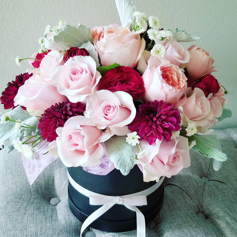 Gift flowers in a black hat box