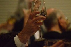 A toast hand raised with glass