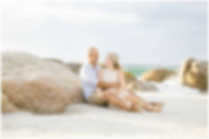 engagement shoot at clifton fourth beach, couple sitting against boulders, pastels