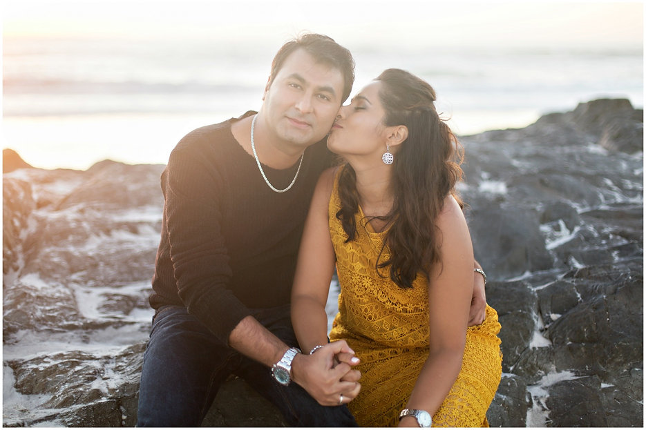 couple sitting on rocks, engagment shoot at the beach, what to wear