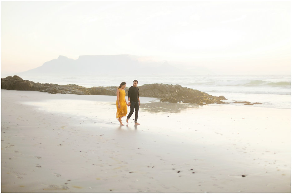 couple walking on the beach with table mountain in the background