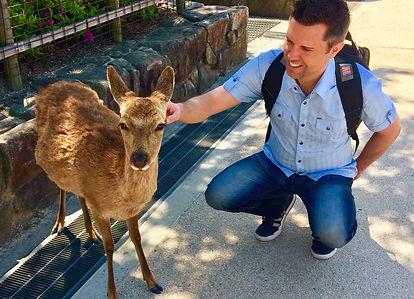man petting deer