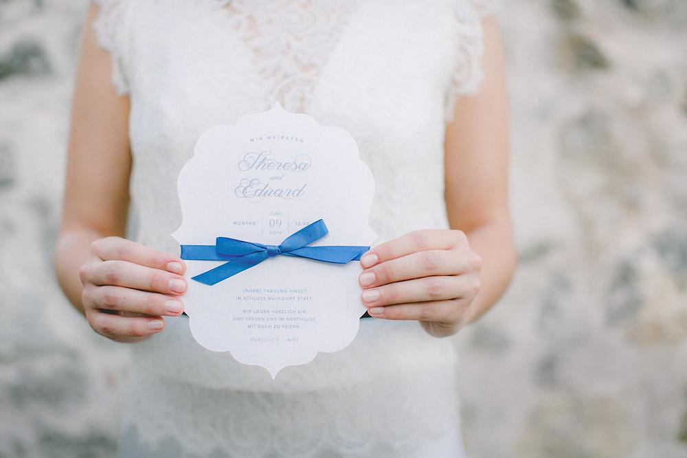 Hochzeitseinladung in geschwungener Form mit blauer Schleife