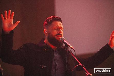 Bruno de olhos fechados em frente a um microfone
