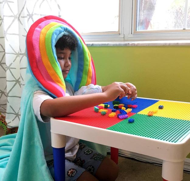 A Child Wears Sveta's Kidswear Rainbow Hooded Blanket playing with blocks