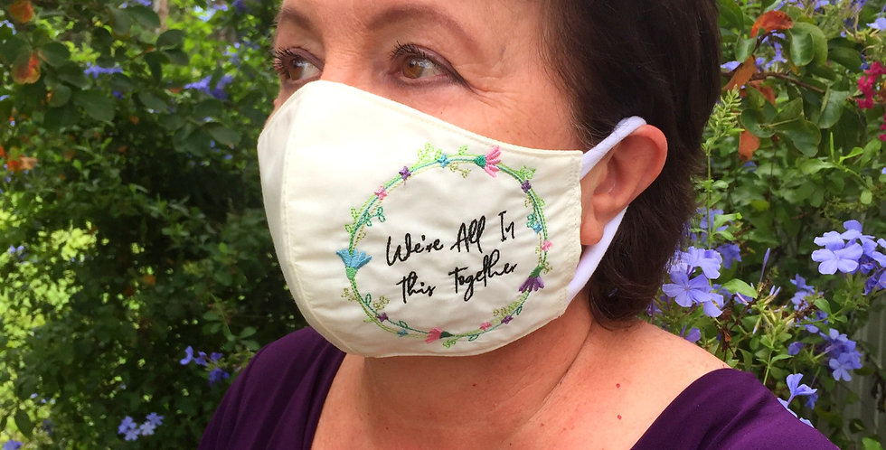 Sveta's Kidswear embroidered, washable adult face mask cream color on a woman