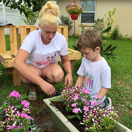 A Woman with Child Gardening in White Embroidered T-shirts.
