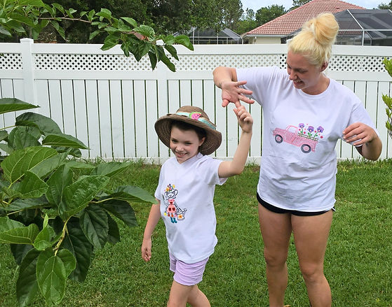 A Woman Twirling with a Girl, wearing White Matching T-shirts.