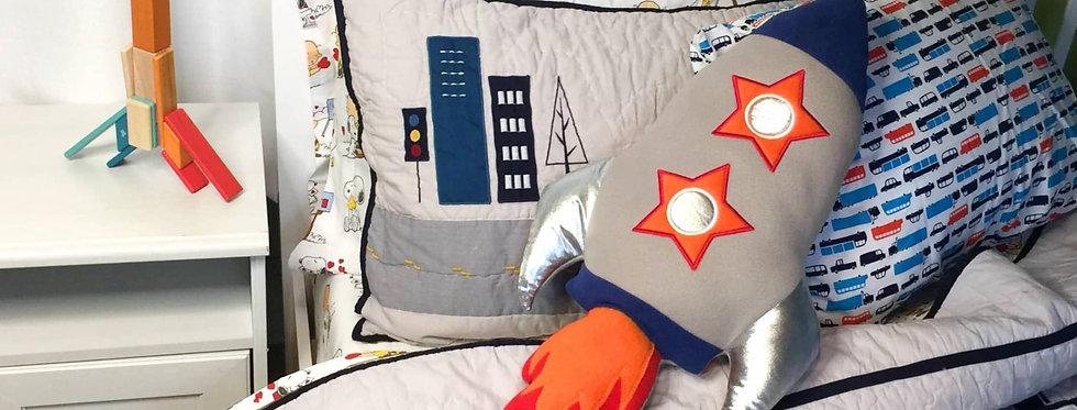 Sveta's Kidswear Rocket Shaped Pillow On Bed.
