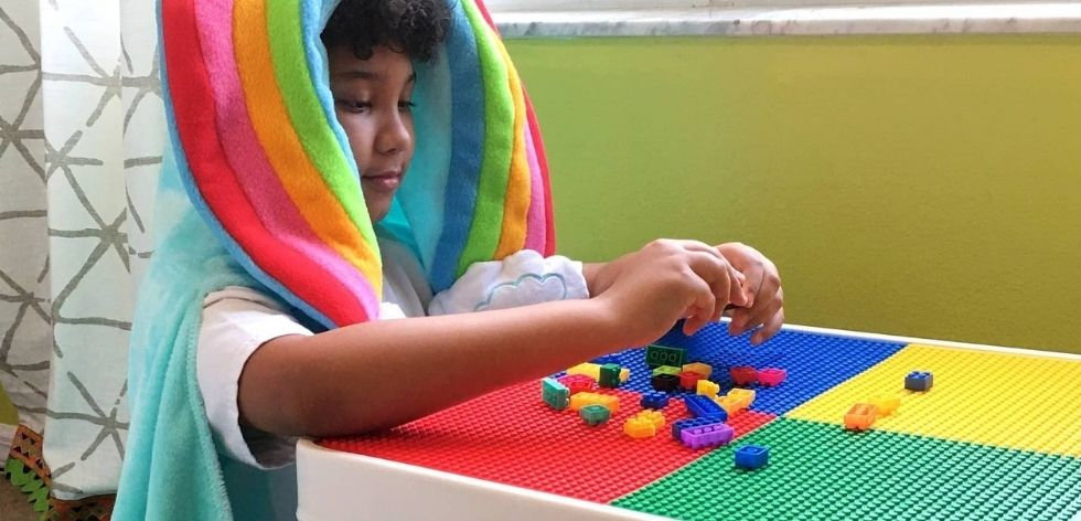 Boy is in rainbow hooded blanket playing with blocks