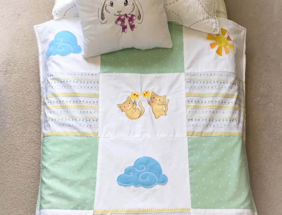 Patchwork Baby Blanket With Embroidered Animals and White Baby Pillow.