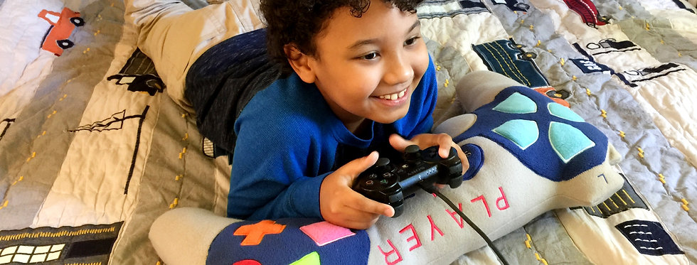 A boy laying on a joystick shaped decorative pillow made by Sveta's Kidswear