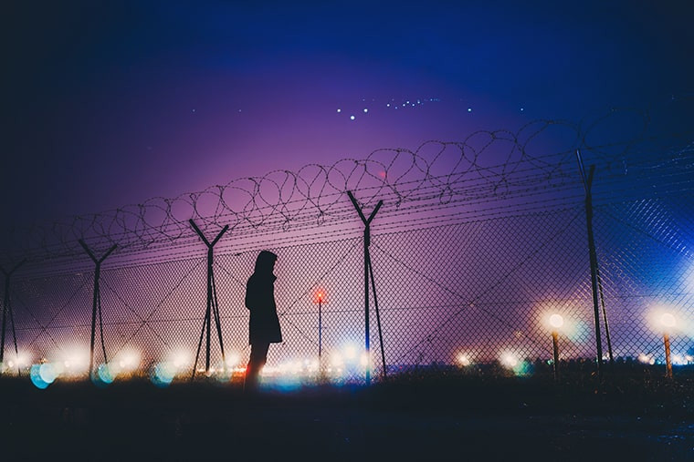 a person behind a wired fence