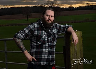 Nottingham wedding photographer leaning on a gate to a field in Annersley, Nottingham