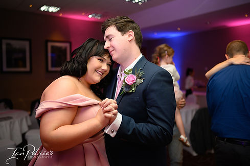 Eastwood Hall weddings with bridesmaid and her partner having a romantic moment shot by Nottingham & Derby Wedding Photographer