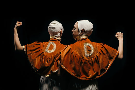 """DoppelDänger wrestling duo. Two individuals, shoulder to shoulder with their backs to us, in matching orange velvet capes with gold collars and a gold capital letter """"D"""" embroidered onto the back of each. They wear white cloth caps that cover their hair, with holes for their ears to poke through. One faces away from us, one turns to look at the other beside them. Each hold their outside arm away from their body, bent elbow, hand making a fist. A stark black background."""