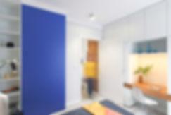 Sypialnia z miejscem do pracy. Duże białe szafy i wkomponowane w nie biurko. Granatowa ściana.
