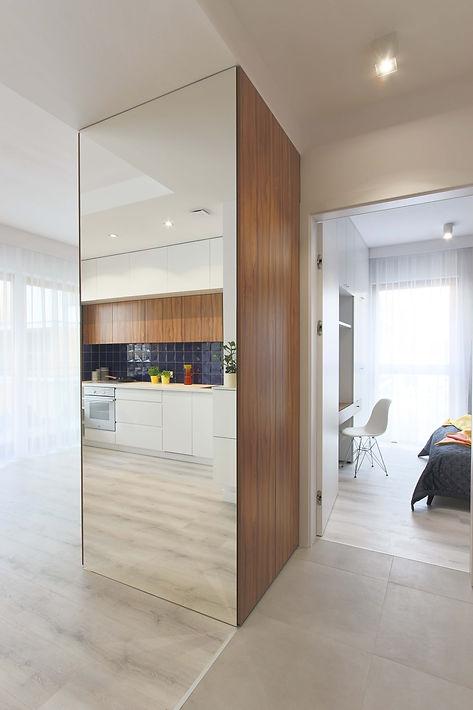 Widok na duże lustro umieszczone na boku mebla. Odbicie wnętrza.