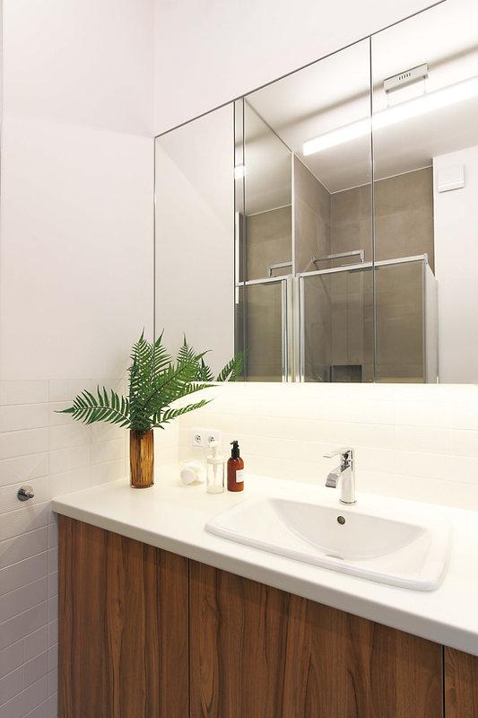 Umywalka nablatowa na białym blacie wspartym na drewnianej szafce. Nad nimi szafki na przybory toaletowe z lustrami.