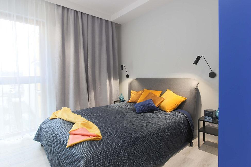 Szaro-granatowa sypialnia. Duże łóżko z pomarańczowymi poduszkami. Kobaltowa ściana.