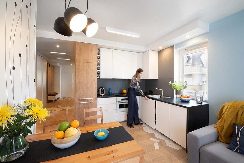 kuchnia z salonem blat pod oknem, podłoga w jodełkę, białe meble kuchenne