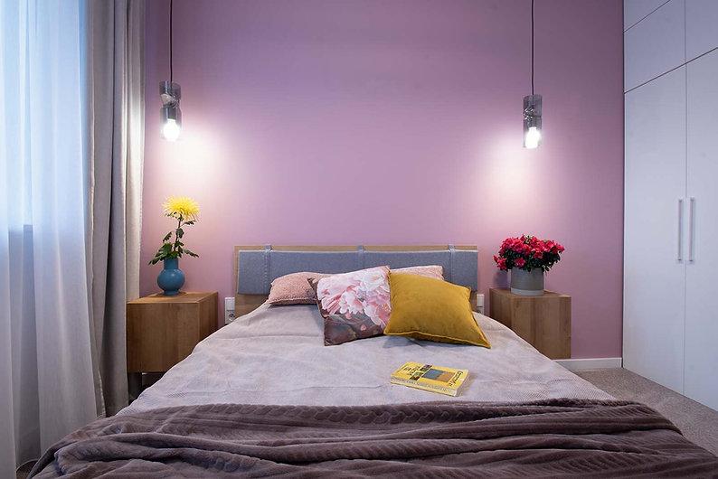 kolorowa sciana w sypialni, łóżko z małym zagłówkiem, dwie wiszące szafki nocne, dwie wiszące lampy