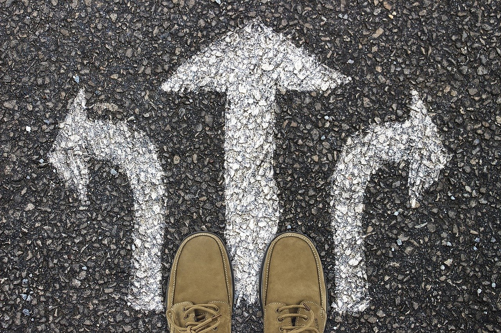 Feet standing on a road surface with three arrows painted on it. Each arrow is pointing in a different direction.