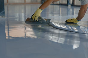 The-worker-applies-gray-epoxy-resin-to-the-new-floor-1295831125_6720x4480.jpeg