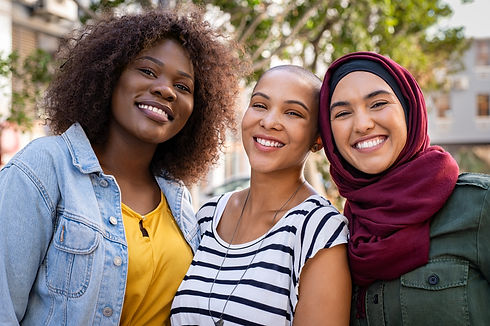 Group of three happy multiethnic friends looking at camera. Portrait of young women of dif