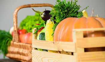 Chemical-free vegetables like pumpkin, eggplant, golden corn, capsicum, dill leaves and coriander in a wicker basket and wooden crate