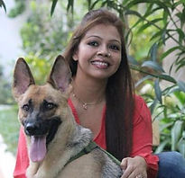 Doggiliciouus' inspiration and brand ambassador Kira sitting in a garden with founder and canine nutritionist and holistic wellness practitioner Manssi SK Saha